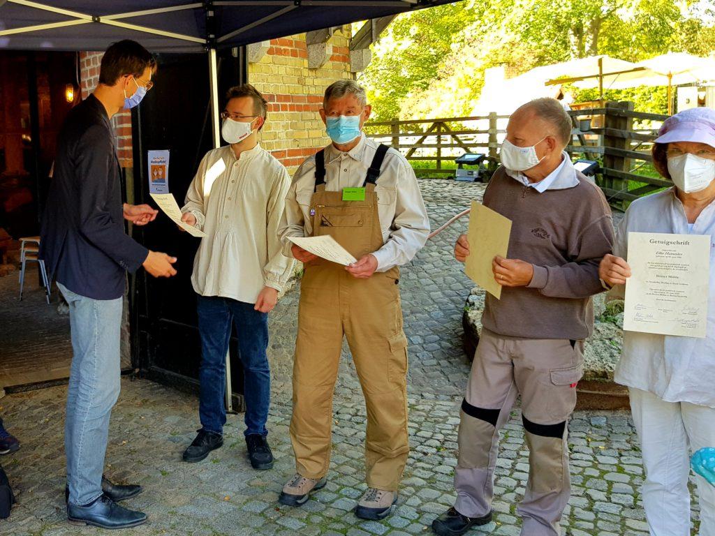 Bezirksbürgermeister Martin Hinkel überreicht den nun fertigen Müllern die Urkunden.